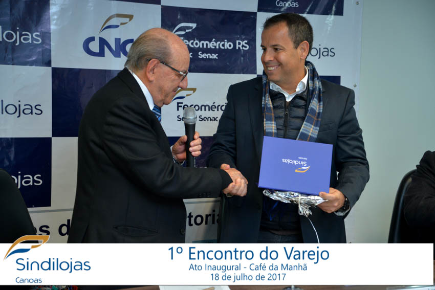 Presidente do Sindilojas Canoas entrega uma homenagem ao palestrante, Leonardo Rangel